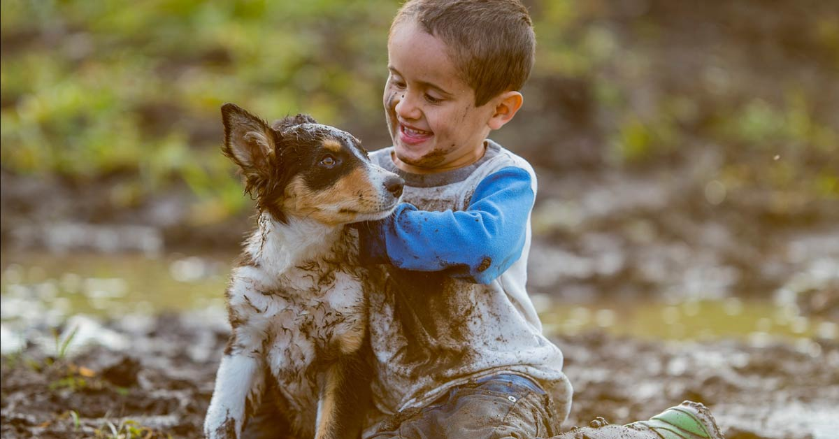 Boy and Puppy Playing in the Mud