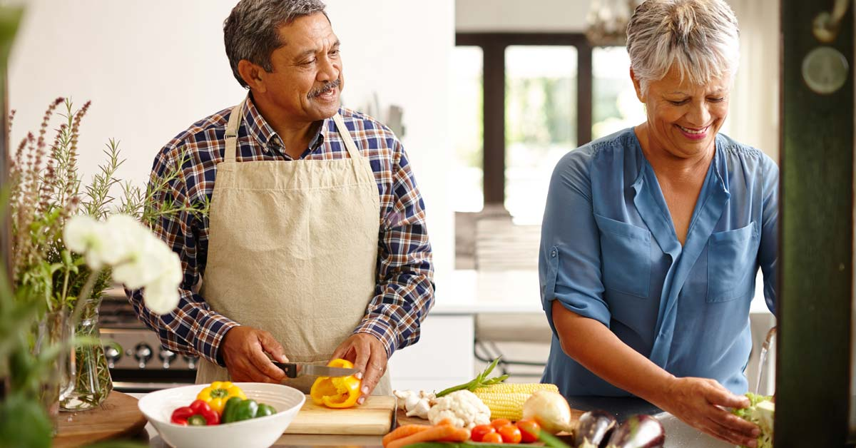 Healthy older couple making dinner