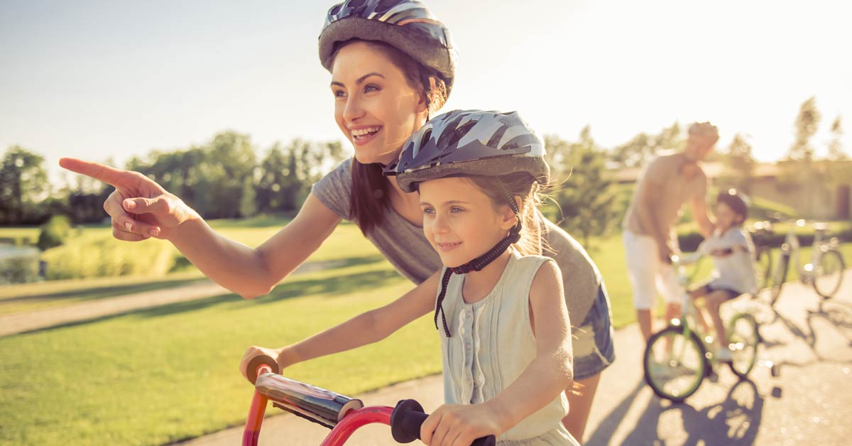 Mom with daughter riding bikes.