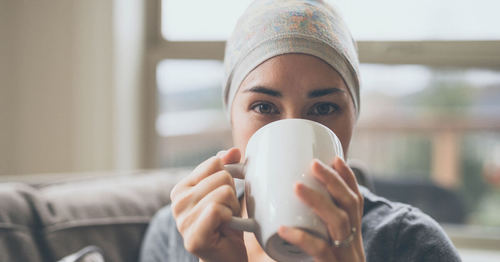 Young woman with cancer drinking tea