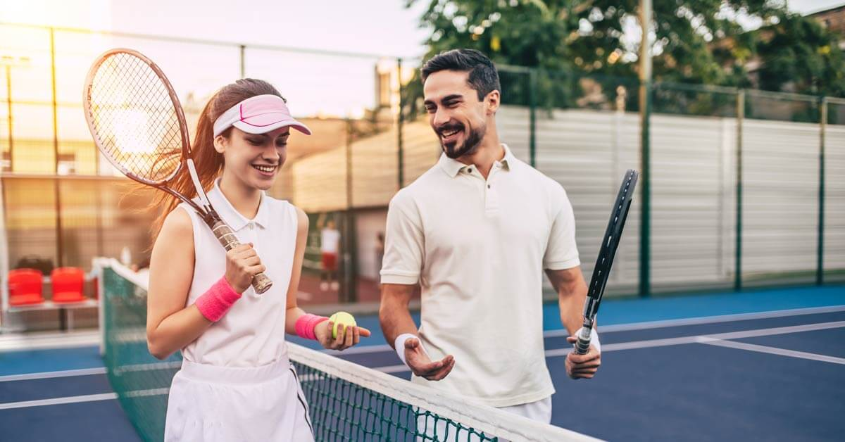 Man and woman getting ready to play tennis together.