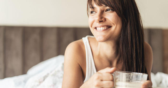 Woman laying in bed with a warm drink.