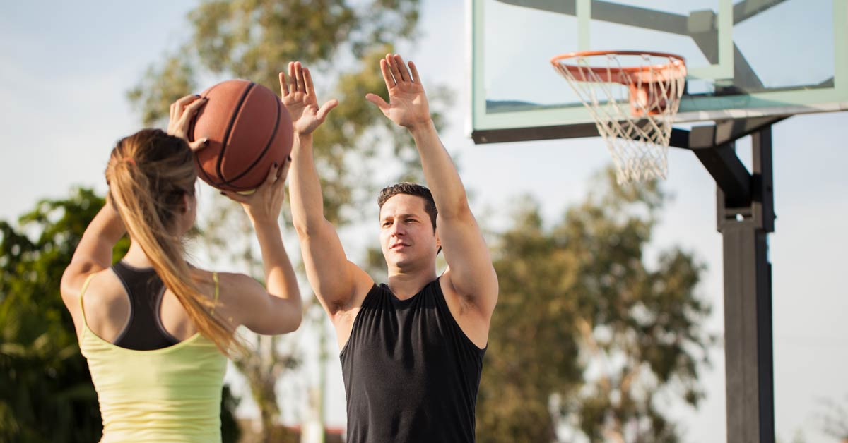 Man and woman playing basketball outdoors.